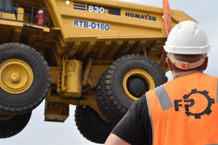 Crane lifting a Komatsu 830E dump truck