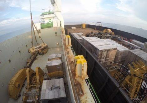 Crane lifting heavy mining machinery onto boat for transportation