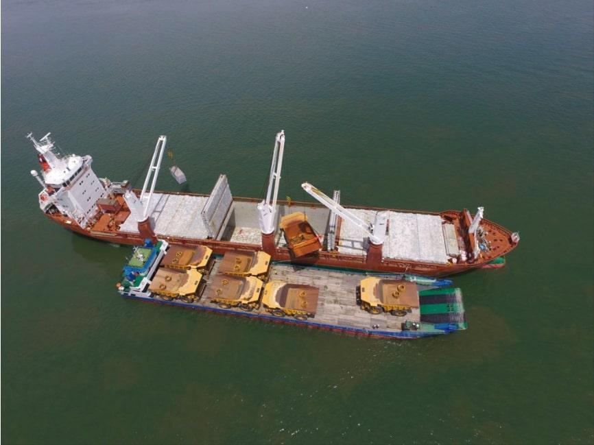 Crane loading mining machines from landing craft to vessel